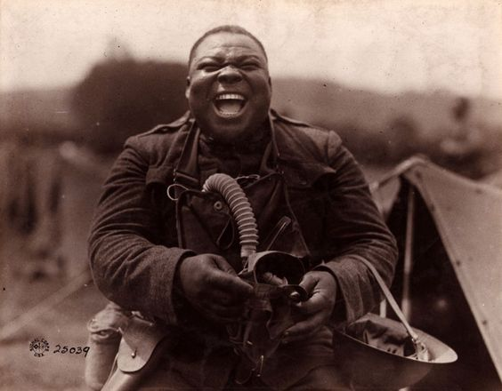 """Big Nims"" WWI Black Soldier holing his gas mask and laughing. .jpg"