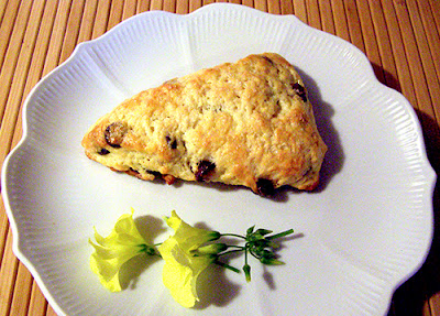 Single scone on plate with flower