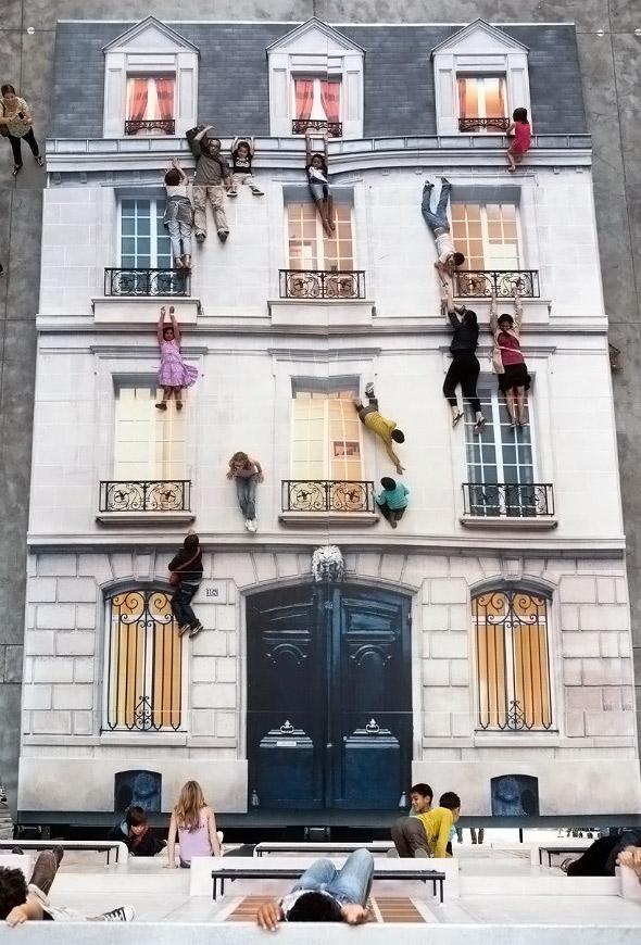 Bir eve tırmanmış ve çıkıntılarına tutunmuş gibi görünen insanlar