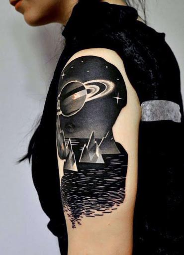 Se você quer se afastar dos azuis e violetas ou laranjas e vermelhos, aqui está um preto-e-branco tatuagem com Saturno e seus anéis bonitos.