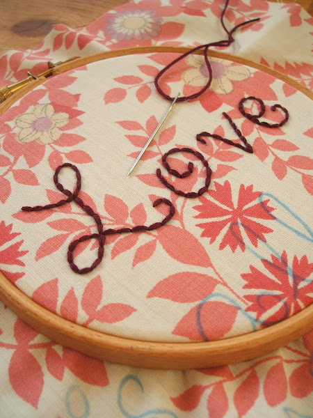 work in progress image of hand embroidered love text onto vintage fabric