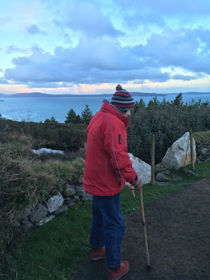Corina Duyn walking with walking sticks at Dzogchen Beara