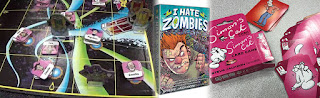 A banner made up of three images fading into one another: on the left, a photo of the board from Bill and Ted's Excellent Board Game (cartoon-style temporal pathways in the style of the original movie) with cardboard pieces representing the players in phone booths and characters from history). In the middle is the cover for I Hate Zombies (a cartoon style man, grimacing in anger and covered in bandages, with a horde of zombies behind him). On the right is the box for the Simon's Cat Card Game next to several of the cards from the game, all decorated with the character from the titular comic.