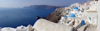 A panoramic photo of the city of Iola, with its characteristic whitewashed buildings, several of which are topped by blue domes, on the craggy island of Santorini, with the Mediterranean Sea visible in most of the left half of the photo.