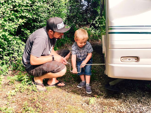 father and young son winding down the legs of a caravan together