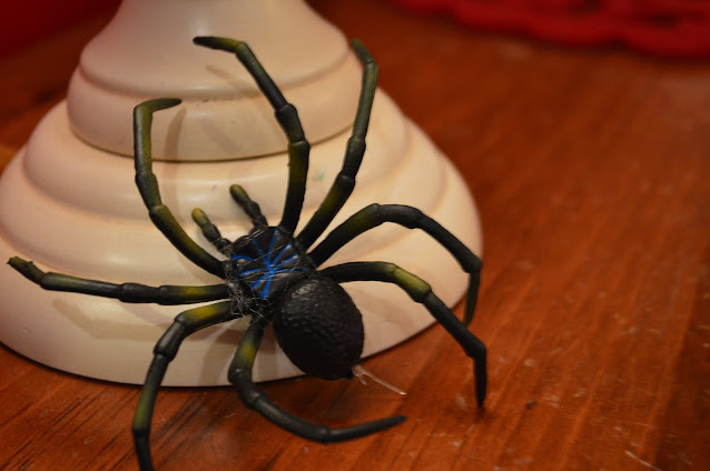 Black Rubber Spider on a white candlestick