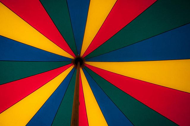 Onderkant van ronde tent met rode, gele, blauwe en groene banen.