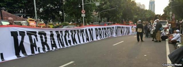 "Spanduk putih berukuran besar bertuliskan ""Pelantikan Anies-Sandi: Kebangkitan Pribumi Muslim"""