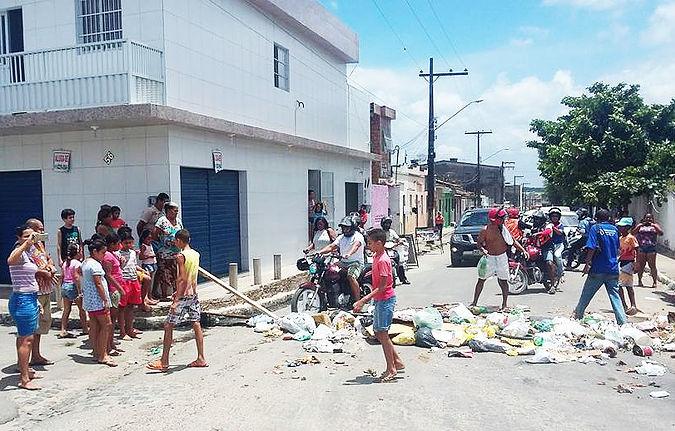 Em protesto, moradores interditam rua com lixo na cidade de Goiana