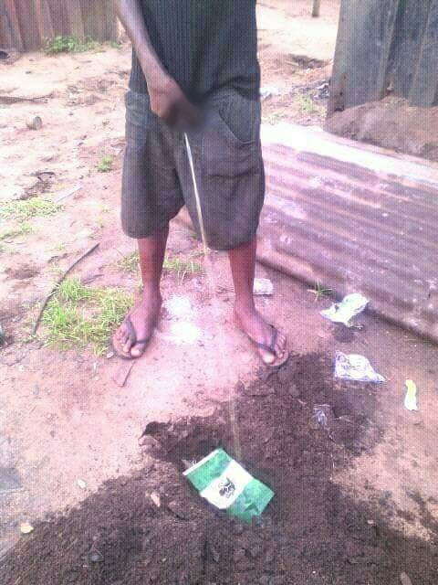 Oct 1: Biafran supporter buries Nigerian flag after urinating, burning it