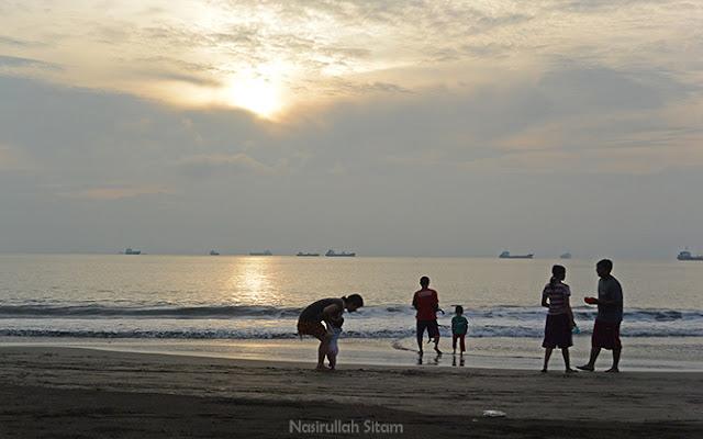 Pengunjung menikmati waktu pagi di pantai bersama keluarga