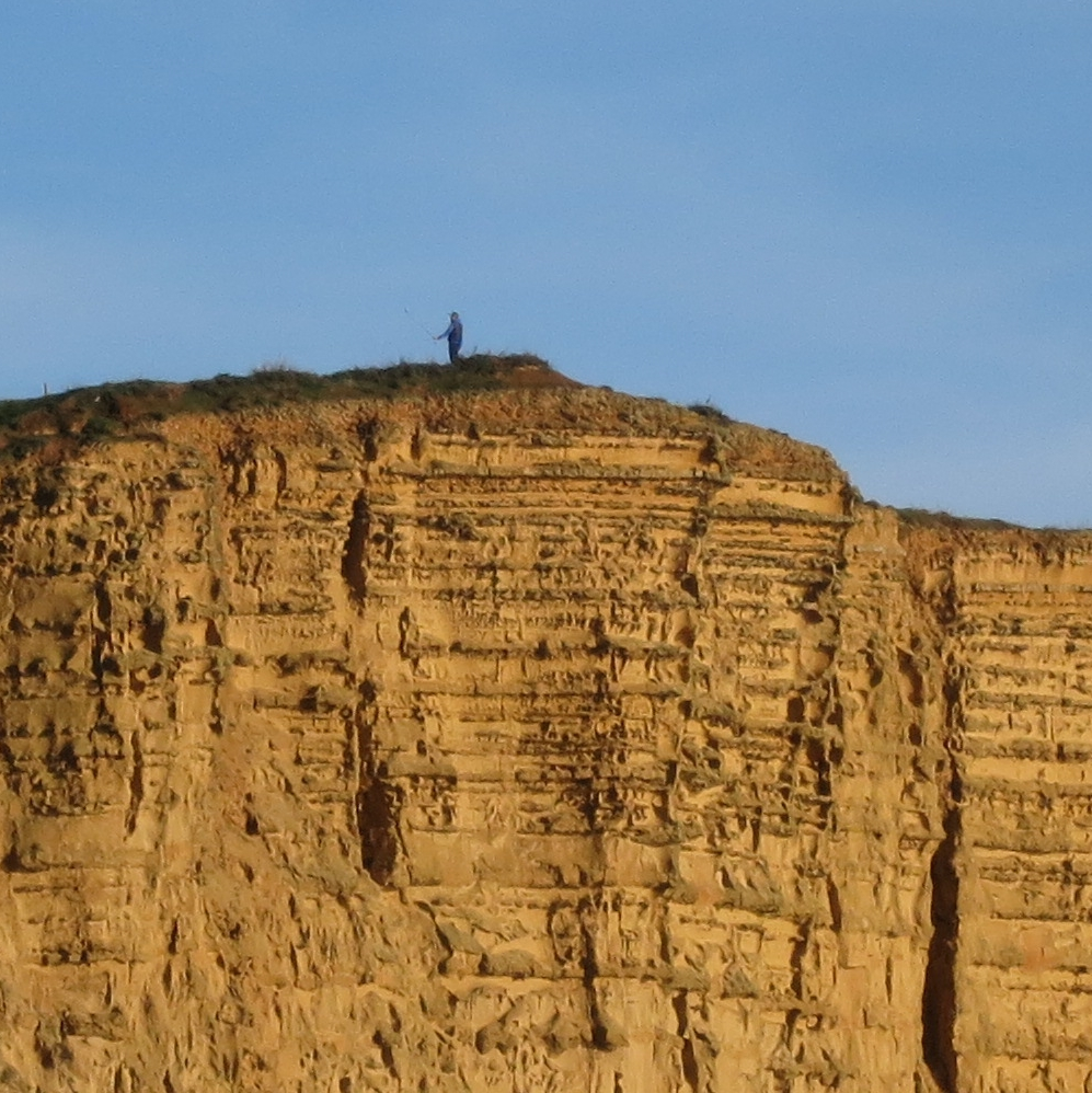 Man on top of cliff at West Bay, Dorset - holding out some kind of stick.