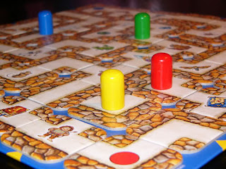 A closeup detail photo of the board with the pawns on it, in the middle of a game. In the foreground is the corner of the board showing the tile with the red dot that indicates the red player's starting position. Each tile shows a section of corridor bounded by stone walls. Some corridors are straight hallways, others are T junctions or right angle turns. Some of these tiles have images on them, such as the old-looking book with a large calligraphy letter A, or the tile with a hobbit-like creature with a tail, or the map on another tile. The four pawns are placed in various places around the board, with the yellow pawn in the foreground sitting on a tile that is arranged so that neither of ends of the right-angle corner on that tile meets up with corridors on adjacent tiles.