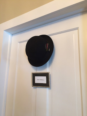 Door to guestroom with bowler hat hung on it above silver frame with room name