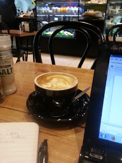 A photograph of a cup of coffee, laptop and notepad in a cafe.