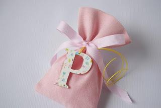 μπομπονιέρες βάπτισης ροζ πουγκί για κοριτσάκι με ξύλινο αρχικό γράμμα και λουλουδάκια