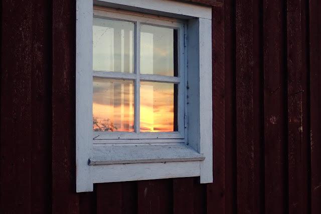 A cottage window, reflecting sunset.