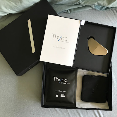 THYNC box opened against a light blue sheet; cover is black with a white slash in the middle; next level has a white manual and the golden kinda-triangular THYNC device; bottom level has a soft carrying case packets with the gel pads for use