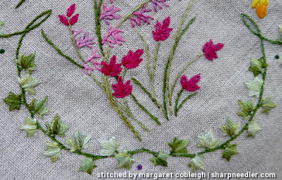 Detail of motif on Herbier showing pink flowers and ivy border. Ivy border is stitched with variegated House of Embroidery threads.
