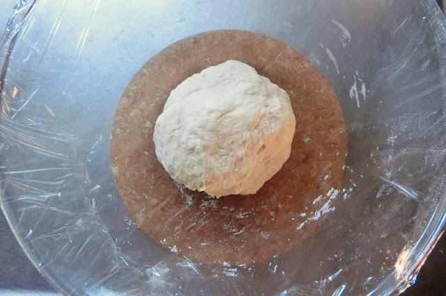 生地を丸くまとめ、ラップをボウルにかぶせて温かい場所で発酵させる