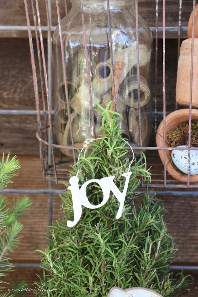 Christmas potting bench decorated with rosemary tree with a joy ornament