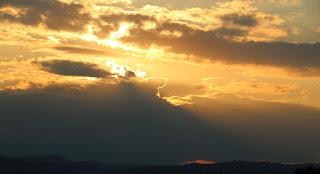 The sun, a disk behind a cloud