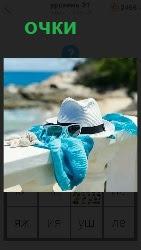 на парапете лежат очки, шляпа и синий платок