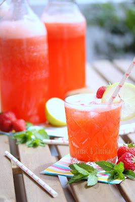 """alt=""""limonade fraise dans 2 bouteilles en verre et un verre décoré d'une paille, d'une fraise et d'une rondelle de citron"""""""