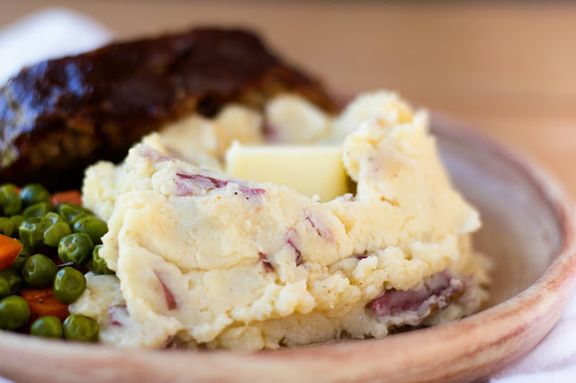 The finished horseradish mashed potatoes, on a plate with steakhouse meatloaf and peas,