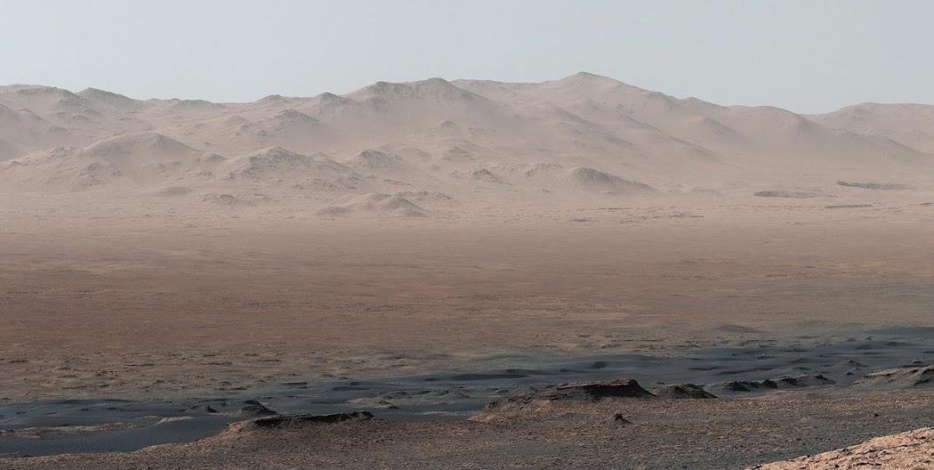 Một vị trí đẹp từ chỏm núi Vera Rubin cho tàu Curiosity phóng tầm nhìn chi tiết về nơi mà nó sẽ bắt đầu nhiệm vụ khám phá bên trong Hố va chạm Gale. Trước mặt là hướng bắc-đông-bắc, hình ảnh được ghép lại từ 8 hình ảnh chụp đơn được chụp bởi máy ảnh gắn ống kính phóng to được trang bị trong con mắt phải của tàu. Hình ảnh này được thực hiện vào ngày 25 tháng 10 năm 2017, nhằm sol 1856. Vào lúc này, Curiosity đang đứng ở cao độ 327 mét và đã đi xa được 17,63 cây số tính từ nơi nó đổ bộ xuống hành tinh này. Hình ảnh: JPL-Caltech/MSSS/NASA.