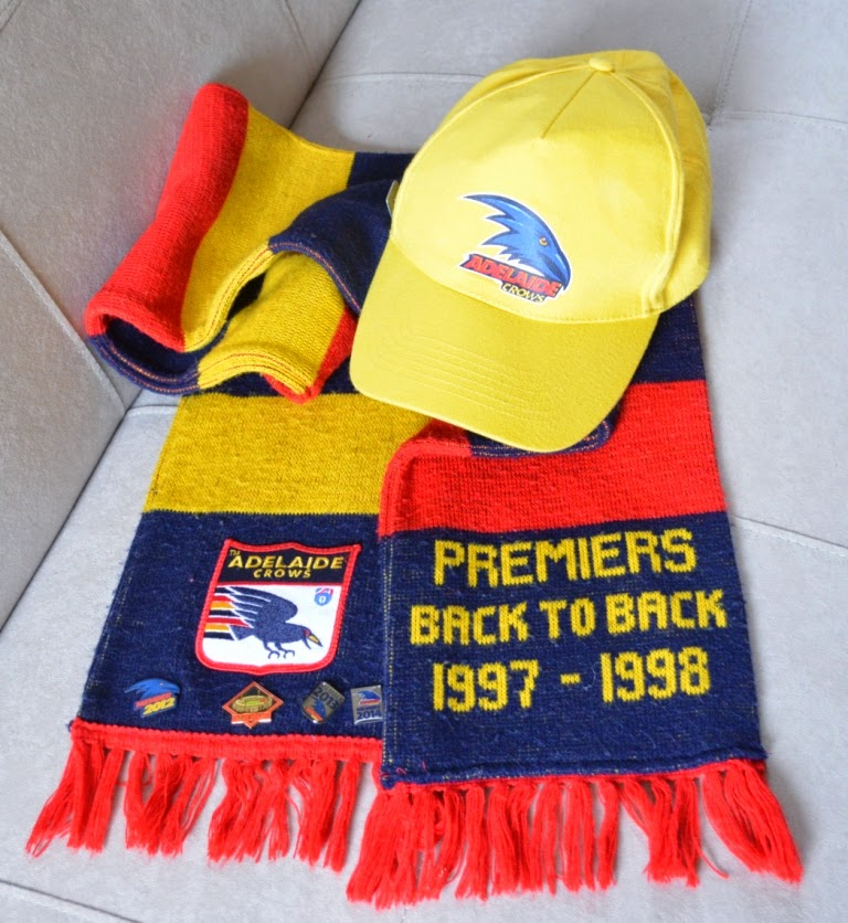 Adelaide Crows hat - yellow baseball cap style with Crow insignia on the front; Crows 'Premiers' scarf with the words 'back to back 1997–1998 on one end and a Crows 'shield' fabric emblem and commemorative pins on the other end.