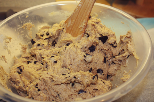 cookie dough with chocolate chunks in a mixing bowl with a wooden spatula, on francescasophia.co.uk