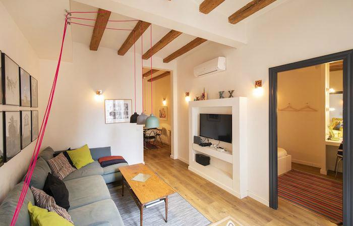 Cómo decorar un apartamento joven con poco dinero: salón con vigas de madera y muebles de pladur
