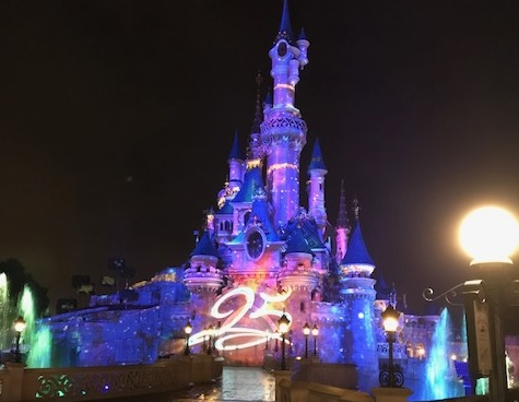 Disneyland Paris castle lit up at night, with 25 at the front as a mark of the anniversary