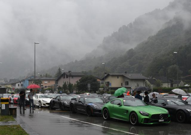 Grüner Mercedes AMG und andere Teilnehmer des Sportcars Day auf dem Parkplatz in Cevio. Tiefe Wolken, Nebel, Regen