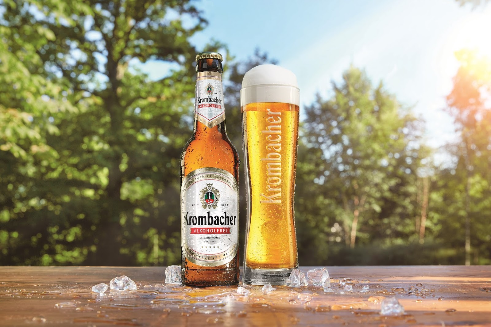 Krombacher beer bottle and filled glass outside in a garden