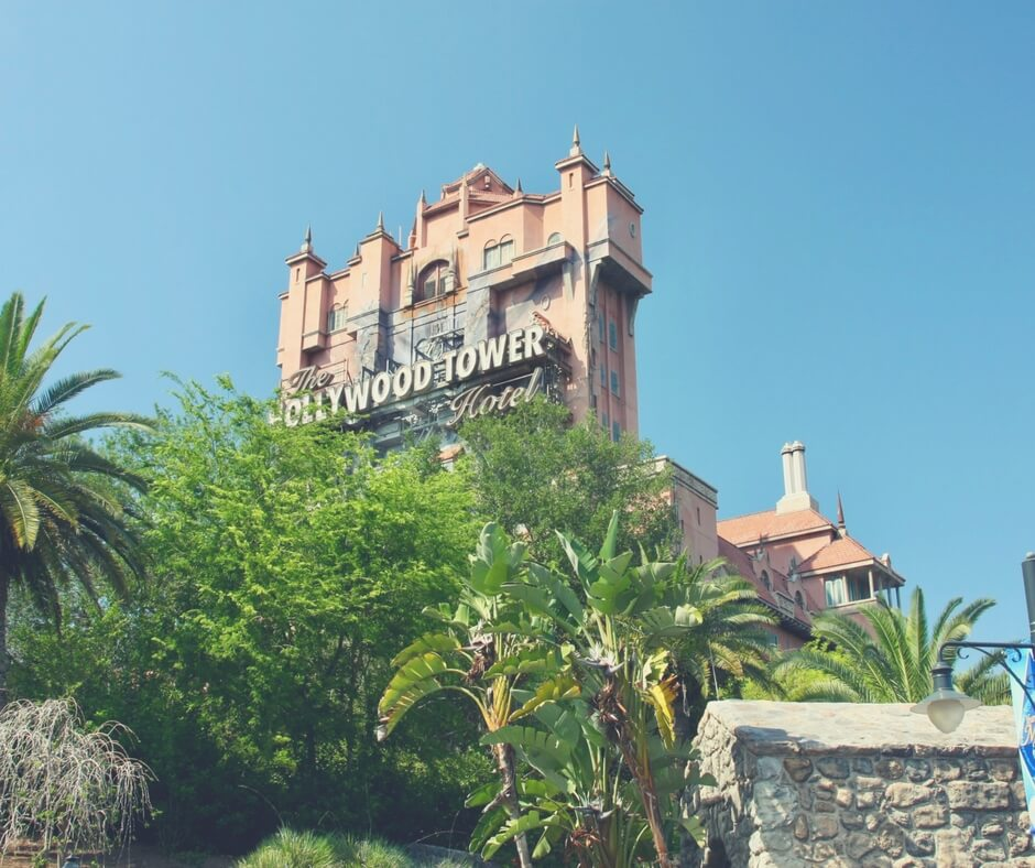 Photo of the Hollywood Tower which features the Tower of Terror in Hollywood Studios. The sky is a clear blue, there are trees blocking the view of the Tower.