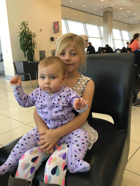 Two little girls sitting in an airport