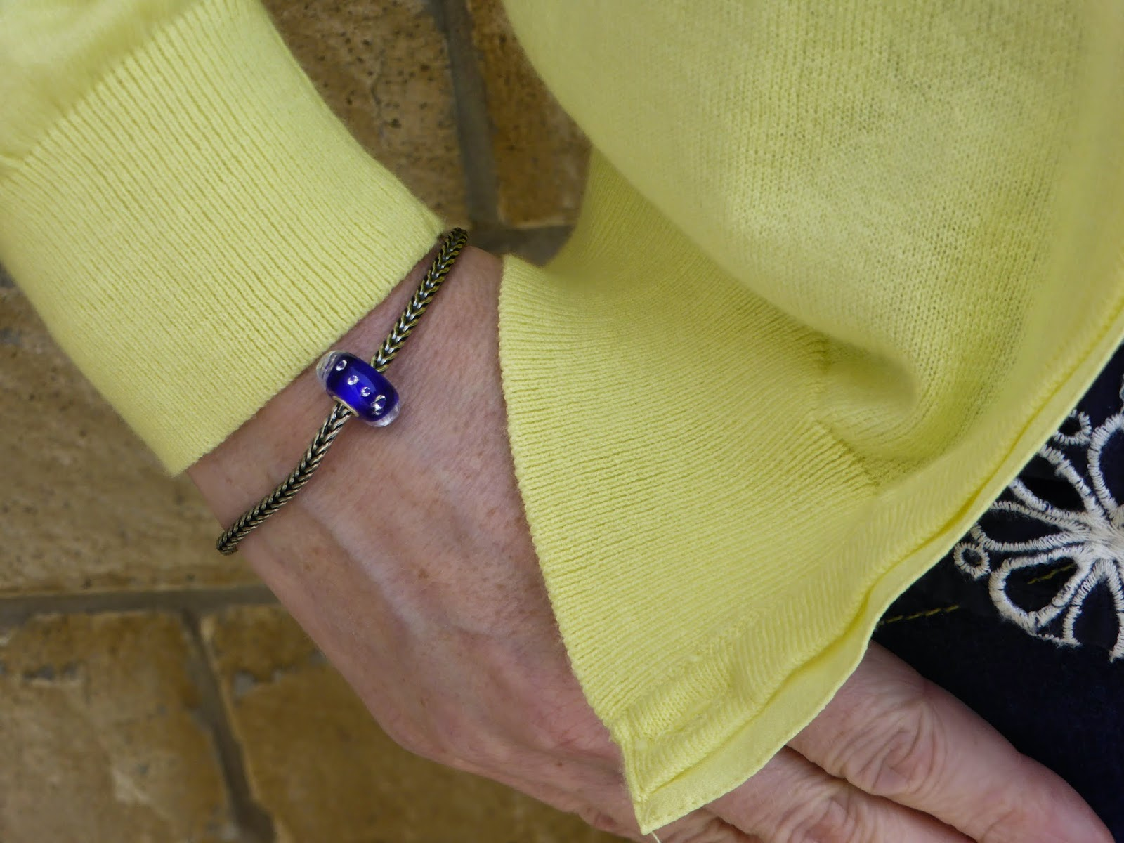 yellow cardigan with  navy top and skinny jeans with trollbeads bracelet