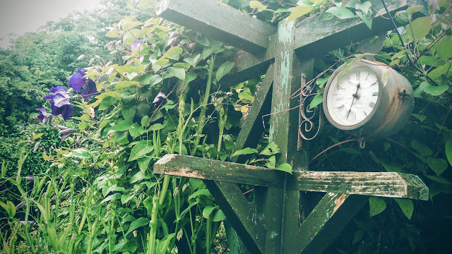 garden clock and clematis blossoms