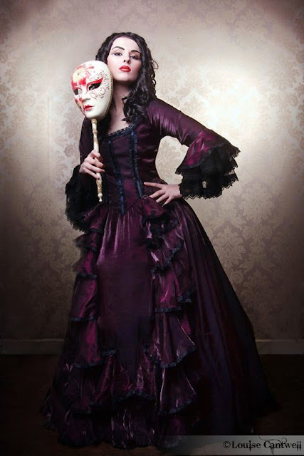 Woman wearing a purple victorian masquerade ball evening gown/dress/ball gown, carrying a venetian mask on a stick.
