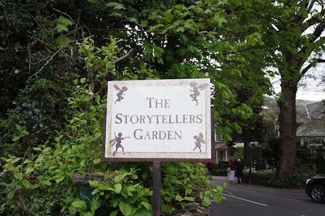 a cream sign reads 'the storytellers garden' in front of a hedge