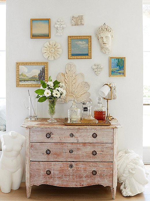 Gorgeous vignette from #PatinaFarm farmhouse with framed paintings and plaster sculptures above rustic chest with #patinastyle