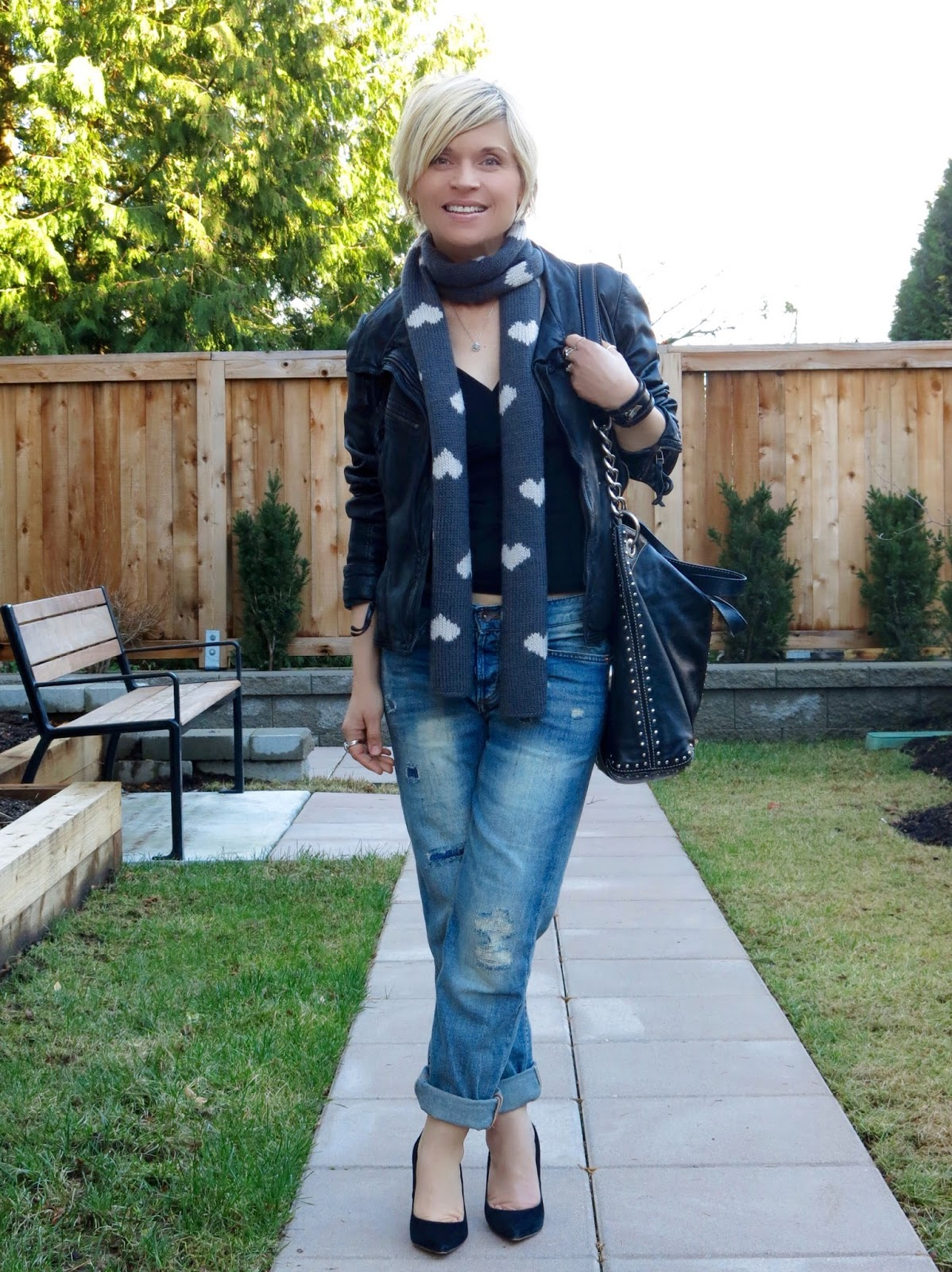 styling boyfriend jeans with a moto jacket, heart-patterned woolen scarf, and black suede pumps