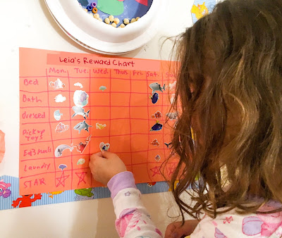 Girl affixes sticker to a chore chart