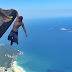 Man is hanging off a cliff but what his GF is doing?