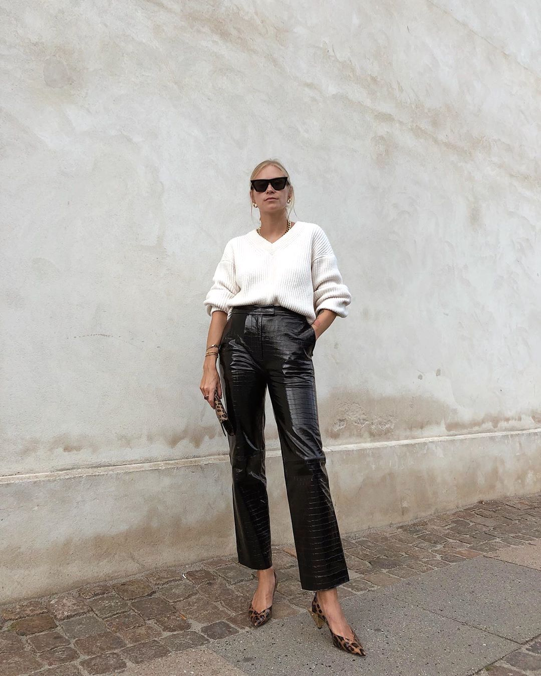 Transitional Spring Outfit Idea — Tine Andreea in square cat-eye sunglasses, white v-neck sweater, black crob patent leather pants, and leopard-print heels