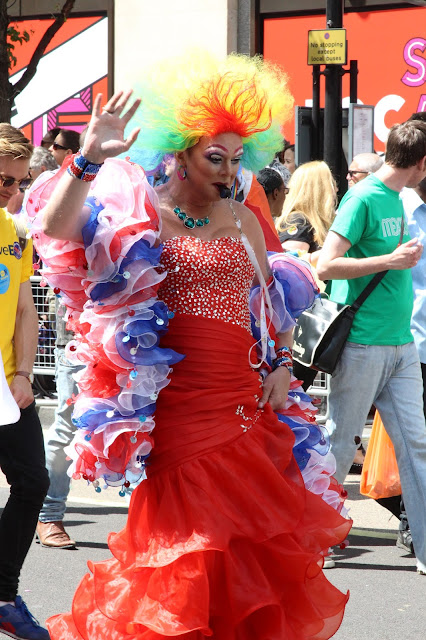 A man in drag (red ball gown and union jack boa) taking part in the 2015 London Pride procession