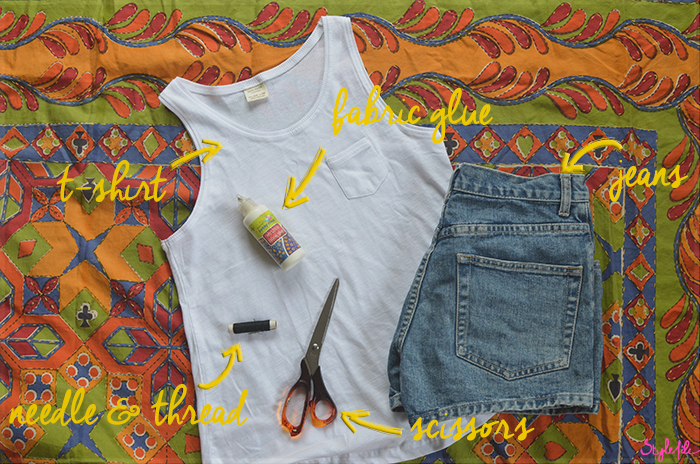 White t-shirt, denim shorts, scissors, fabric glue and needle and thread are the items needed for the DIY tutorial of the Denim Pocket Patch trend