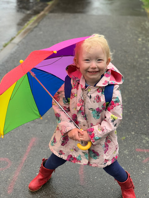 A toddler with a rainbow umbrella, pink flowery coat and a wet day